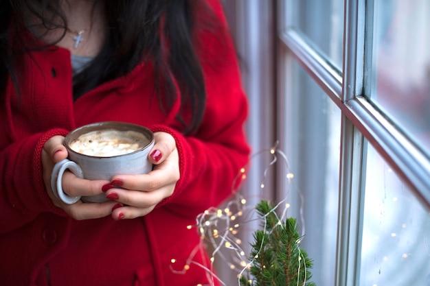 Mok koffie met marshmallow in handen van een vrouw in een rode trui, bij het raam