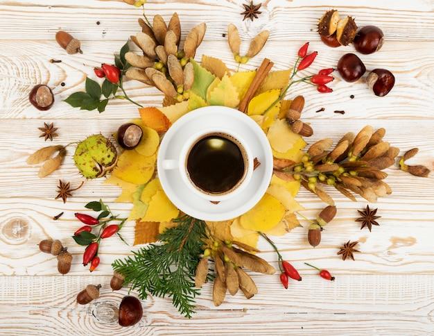 Mok koffie omgeven door bladeren, herfstboomzaden en geurige kruiden