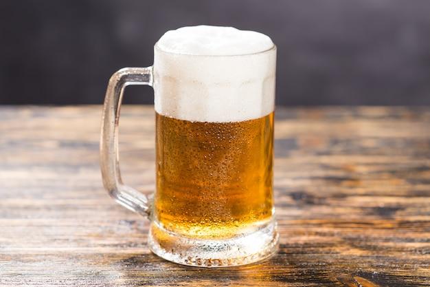 Mok koud bleek bier op een rustieke houten tafel met kopie ruimte.
