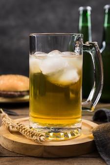 Mok met bier en hamburger naast