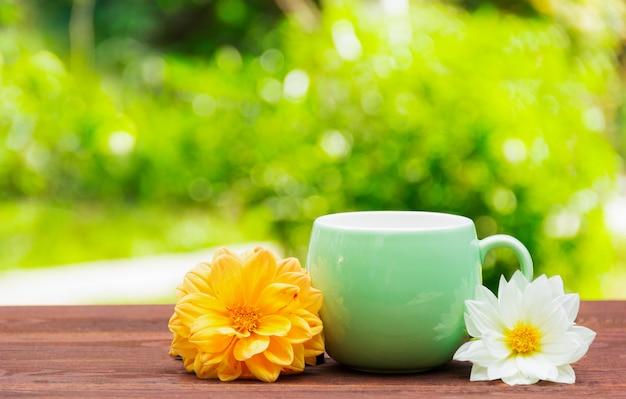 Mok met bloemen op een groene onscherpe achtergrond. een kopje thee in de zomertuin. kopieer ruimte