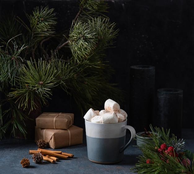 Mok met cacao, marshmallow op een donkerblauwe achtergrond met kaneel, kaarsen, geschenken en dennenboom. donker en sfeerbeeld