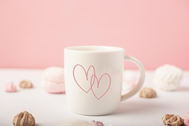 Mok met hartjes en snoepjes op een roze achtergrond. valentijnsdag concept. banner.