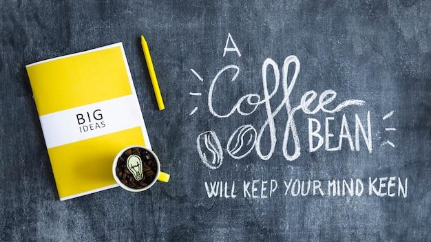 Mok met koffiebonen met gloeilamp over het grote ideeënboek en de tekst op bord