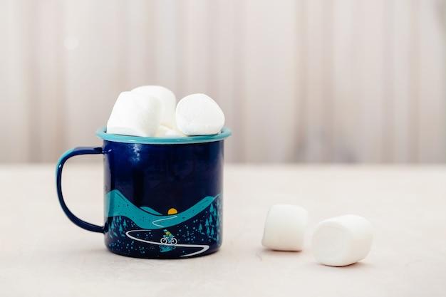 Mok met lekkere marshmallows op lichte houten tafel, close-up. winter voedsel achtergrond concept.