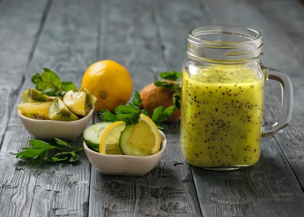 Mok met smoothies van kiwi, komkommer, citroen, peterselie en munt op een rustieke zwarte tafel