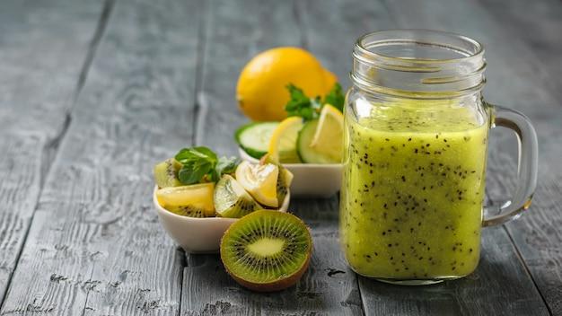 Mok met smoothies van kiwi, komkommer, citroen, peterselie en munt op een tafel