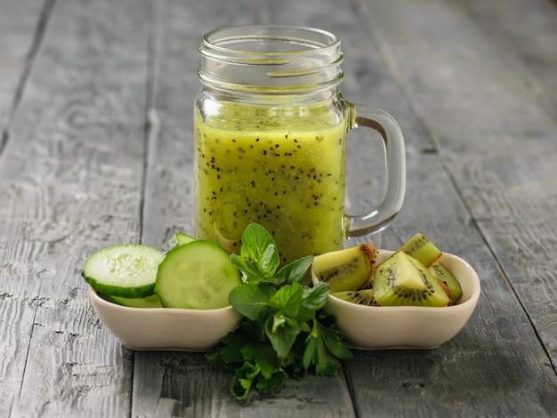 Mok met smoothies van kiwi, komkommer, citroen, peterselie en munt op een zwarte rustieke tafel