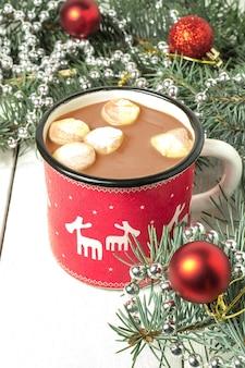 Mok met warme chocolademelk en marshmallows kerstversiering op witte houten tafel