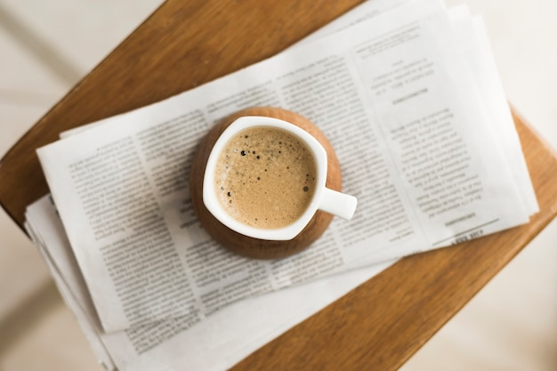 Mok met warme koffie op kranten
