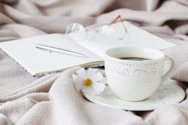 Mok ochtendkoffie in bed, het lezen van een boek, lentebloem