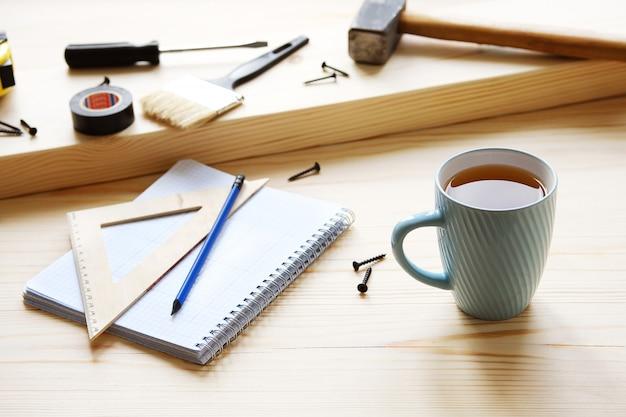 Mok, tekeningen en bouwgereedschap voor het bouwen van een huis of appartementrenovatie.