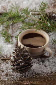 Mok thee en groene kerstboom op sneeuw op houten tafel