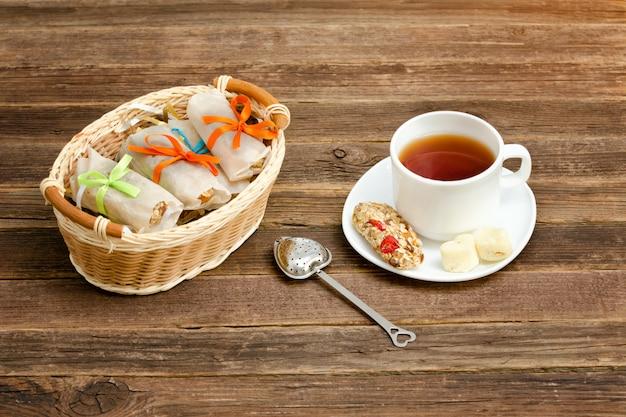 Mok thee, mueslirepen en theezeefje. rieten mand met staven. bruine houten achtergrond