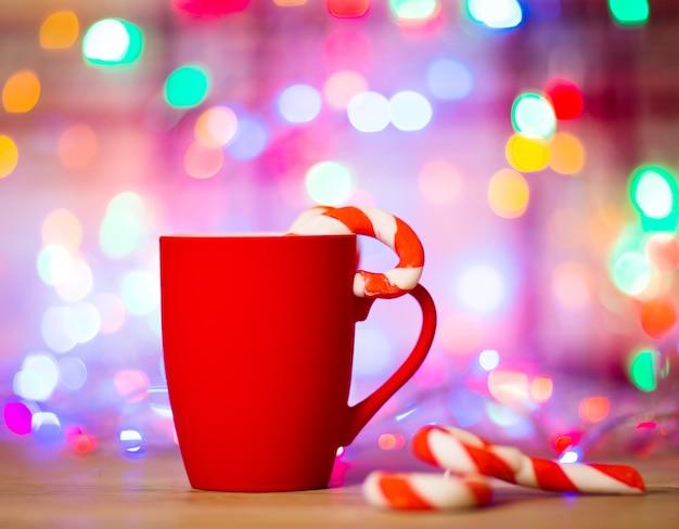 Mok thee of koffie. snoepgoed. kerst versiering. rode ballen en klokken. houten achtergrond.