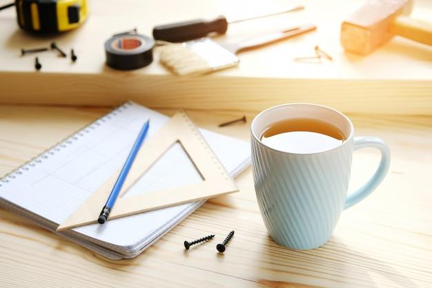 Mok thee, tekeningen en bouwhulpmiddelen voor de bouw van een huis of flatvernieuwing, op een houten lijst. de werkplaats van de voorman. het thema van thuis en professionele reparatie, bouw.