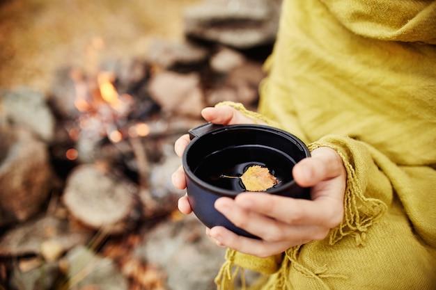 Mok van hete thee herfst in bos in gele gebladerte