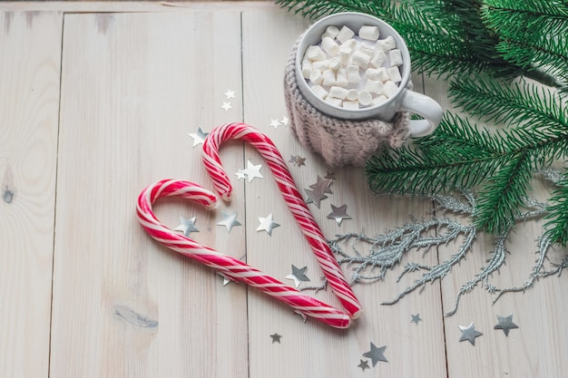 Mok van marshmallows en zuurstokken omgeven door kerstversiering op een houten tafel