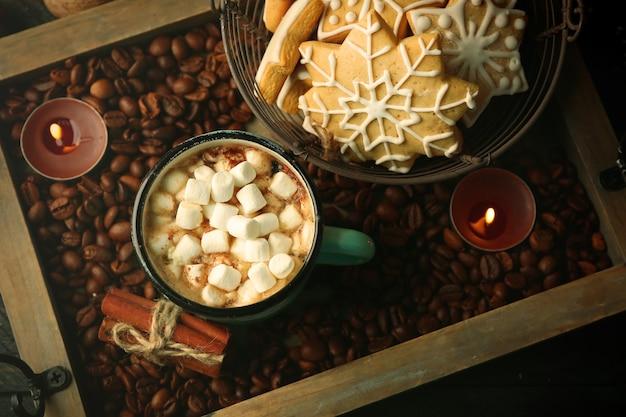 Mok warme cacao met marshmallow en koekjes op koffiebonen