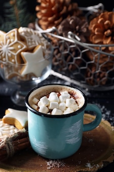 Mok warme cacao met marshmallow en koekjes op zwarte tafel