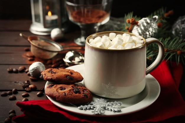 Mok warme chocolademelk met marshmallows, dennenboomtak op houten oppervlak