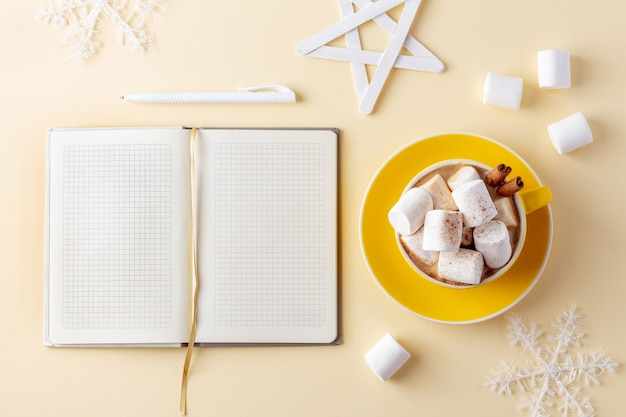 Mok warme chocolademelk met marshmallows naast papieren blocnote