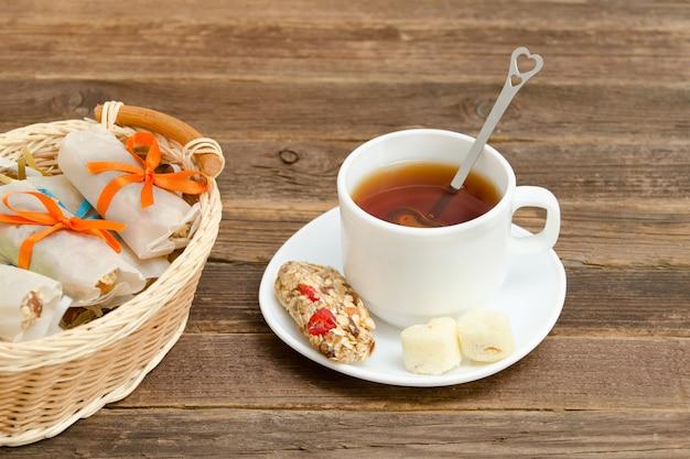 Mok zwarte thee, een reep muesli en een mand met repen