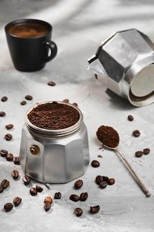 Mokapot gevuld met gemalen koffie, close-up, selectieve aandacht, grijs minimalistisch neutraal oppervlak. kopje espresso koffie op tafel, italiaanse koffie maken in een geiser koffiezetapparaat
