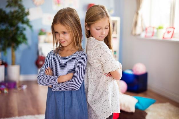 Mokkelende meisjes staan rug aan rug