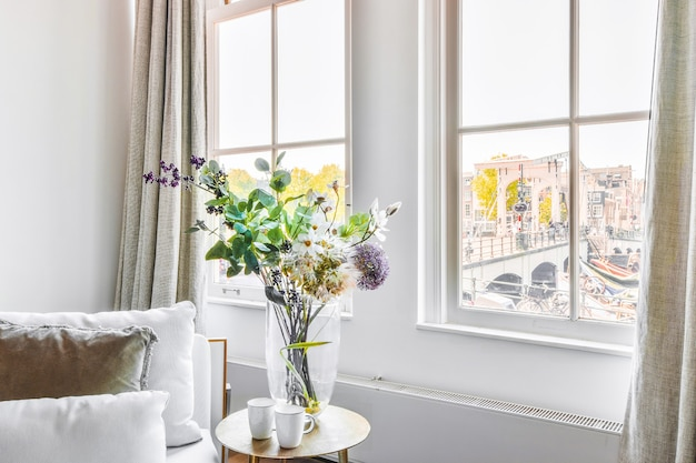 Mokken en vaas met boeket bloemen op tafel in de buurt van bank en ramen in lichte woonkamer in appartement