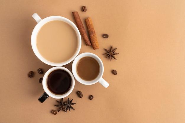 Mokken met koffie met kaneel en anijsplant ernaast