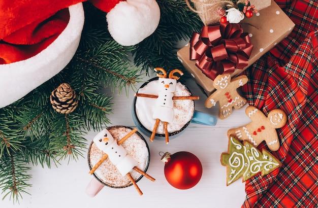 Mokken met warme chocolademelk waarin de mannen uit de marshmallow ontspannen.