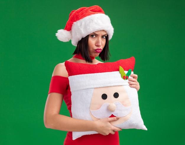 Mokkend jong meisje die santahoed dragen die het hoofdkussen van de kerstman met samengeknepen lippen houden die op groene muur worden geïsoleerd