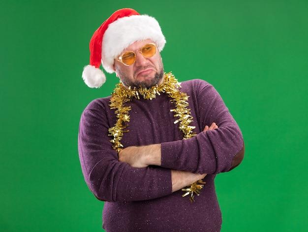 Mokkend man van middelbare leeftijd met kerstmuts en klatergoud slinger rond nek met bril permanent met gesloten houding kijken kant geïsoleerd op groene achtergrond