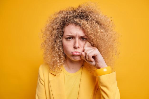 Mokkende huilende vrouw heeft depressief slecht humeur veegt tranen af klaagt over moeilijk leven jankt met overstuur uitdrukking draagt stijlvolle kleding geïsoleerd over gele muur. negatieve emoties concept