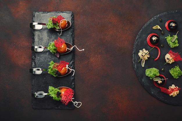 Moleculaire moderne galantineeend van de keuken in lepels op steen en roestige achtergrond