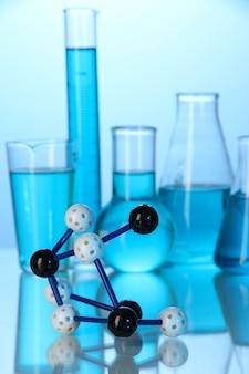 Molecuulmodel en reageerbuisjes met vloeistof op blauw