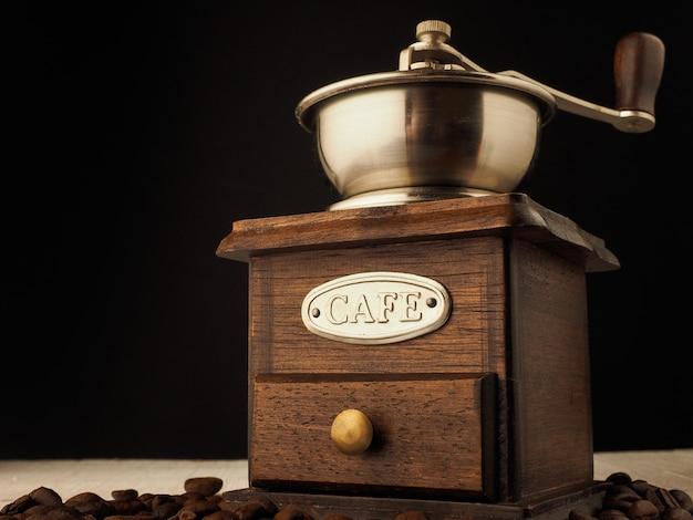 Molen van de close-up de uitstekende koffiemolen met koffiebonen op een donkere en lichte houten achtergrond.