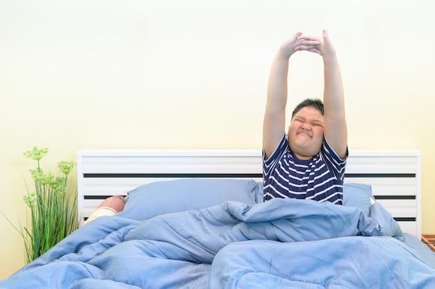 Mollige jongen die zich uitstrekt in bed na het wakker worden