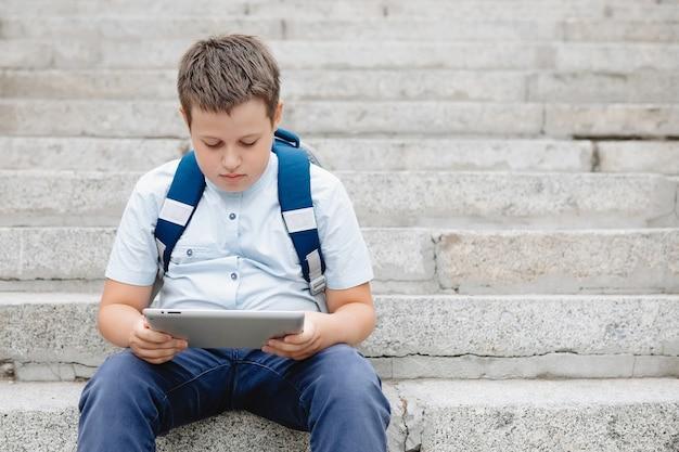Mollige tiener met een tablet en rugzak zit op de trap.