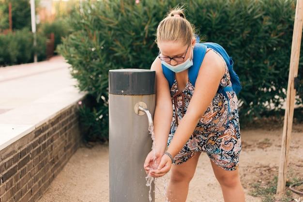 Mollige vrouw met gezichtsmasker drinkwater uit de fontein