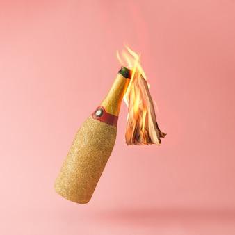 Molotov cocktail gouden champagnefles op roze oppervlak