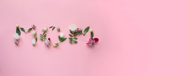 Mom letters gemaakt van bloemen op roze achtergrond. moederdag concept