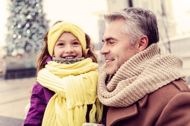 Moment van geluk. blij meisje dat haar glimlach demonstreert terwijl ze met haar vader communiceert