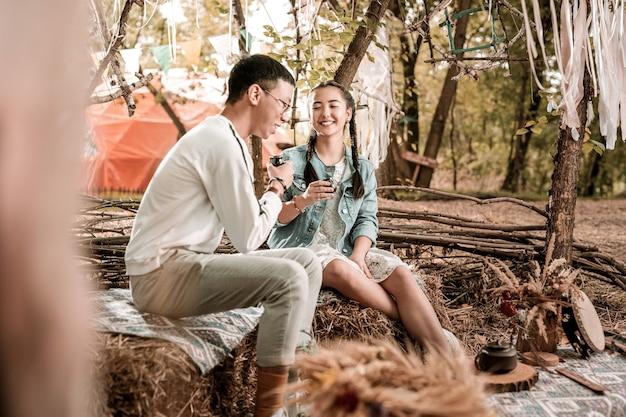 Moment van geluk. tevreden man zit in halve positie en praat met zijn vriendin