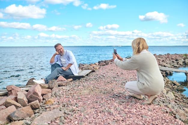 Moment vastleggen. blonde vrouw gehurkt met smartphone fotograferen bebaarde man zittend op de grond in de buurt van zee