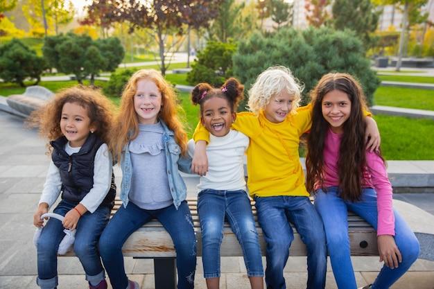 Momenten. interraciale groep kinderen, meisjes en jongens die samen spelen in het park in de zomerdag. vriendschap kent geen ras. geluk, jeugd, onderwijs, diversiteitsconcept. kijk blij en oprecht.