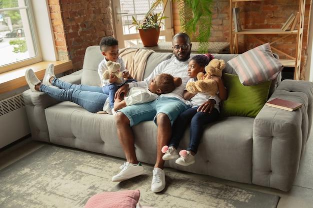 Momenten jonge en vrolijke afrikaanse familie tijdens quarantaine-isolatie tijd doorbrengen