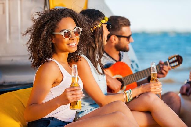 Momenten van geluk. gelukkige jonge afrikaanse vrouw die bier vasthoudt en glimlacht terwijl ze samen met haar vrienden op het strand zit