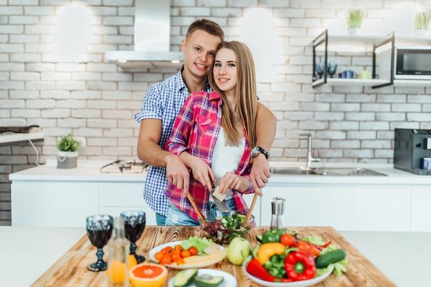 Momenten van intimiteit. mooi jong paar kokend diner bij moderne keuken.